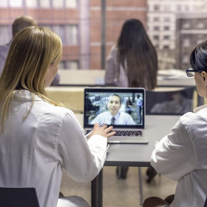 Two female doctors having video conference with  colleague.